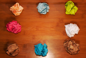 crumpled colorful paper on wooden background creative process