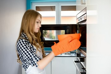 Young blond woman pulls out a hot bowl of  microwave