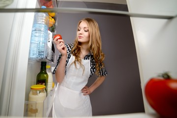 A woman pulls out a tomato from the refrigerator.