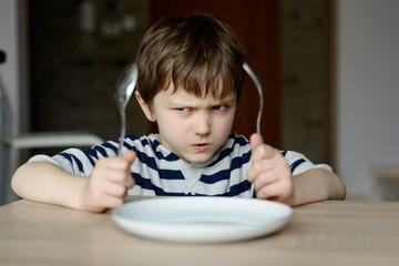 Upset little boy waiting for dinner