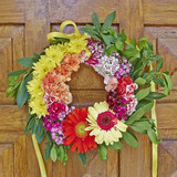 colorful flowers wreath hanging on wooden door closeup