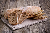 Tasty bread with wheat on wooden background.