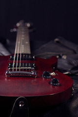 Electric guitar lying on black leather jackets