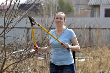 The woman in a garden cuts off branches secateurs with long hand