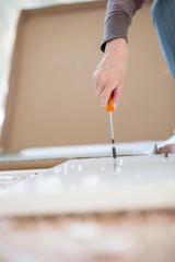 Female hands using a screwdriver