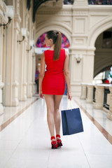 Beautiful smiling girl in a red dress, holding shopping bags