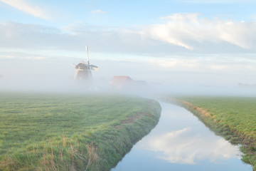 windmill in morning fog by river