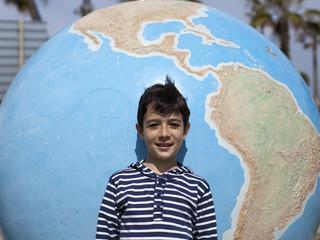 Niño apoyado en bola del mundo