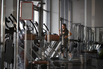 young woman runs on treadmill, exercise in the sport club