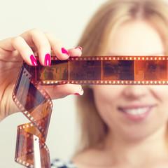 Улыбающаяся женщина рассматривает кадры фотопленки.