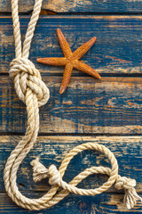 Blue wooden background with starfish and marine rope