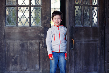 Portrait of cute little boy near wooden door