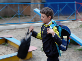 Boy  with backpack walking blurred motion image, focus on face