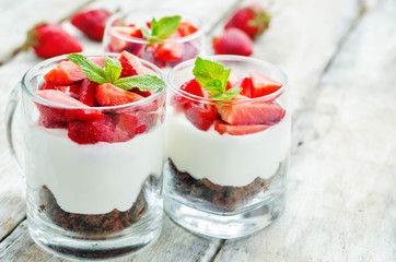 layered dessert with strawberries, chocolate biscuit cake and cr