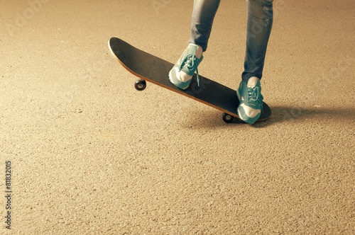 Female on skateboard legs and a lot of copyspace on asphalt - 81832015