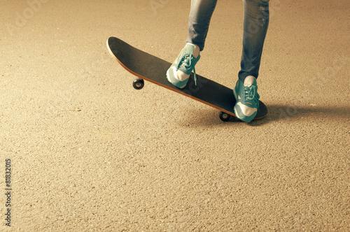 Leinwandbild Motiv Female on skateboard legs and a lot of copyspace on asphalt