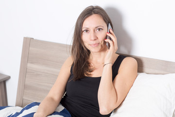 Woman talking on phone in bed