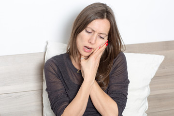 Mid-adult woman sitting in bed with toothache