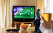 Leinwanddruck Bild - TV watching (football match) with feet on table and snacks