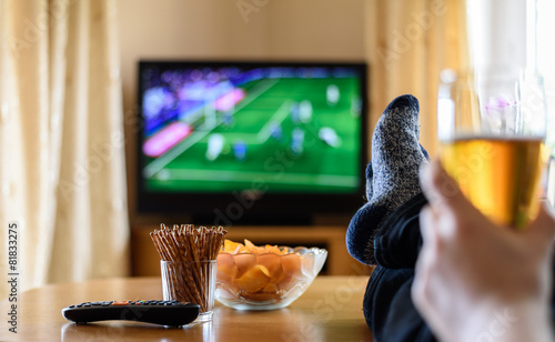 Fotobehang Voorgerecht TV watching (football match) with feet on table and snacks