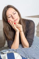 Frau wacht mit Zahnschmerzen auf