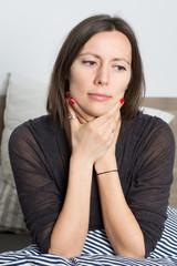 Frau mit Halsschmerzen im Bett