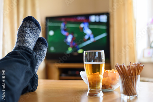 Leinwanddruck Bild TV watching (football match) with feet on table and snacks