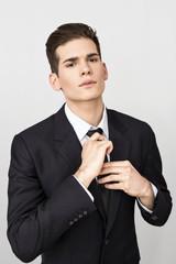 Young man adjusting his tie
