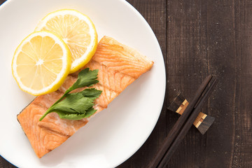 Top view grilled Salmon with lemon on dish.