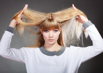 Damaged dry hair. Woman holding hands long hair.