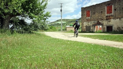 mountain bicycle riding on a country road, old house in ruins