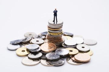 積み上げた硬貨の上にビジネスマンの人形