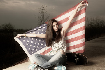 Cute casual girl holding stars and stripes behind her head