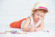 happy little artist  girl in a hat draws pencil