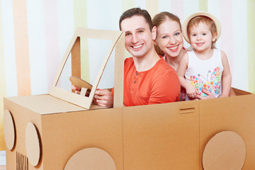 Happy family mother, father, daughter ride on toy car made of ca