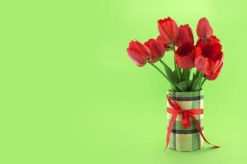 Bouquet of red tulips on green background. Spring flowers.