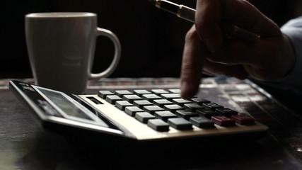Business man typing on calculator drinking coffee, tea