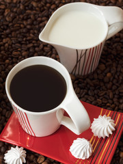 Cup of coffee with saucer, milk jug and coffee beans