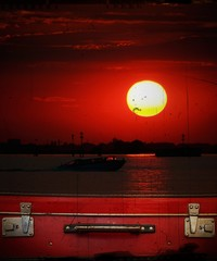old suitcase against a red sunset