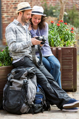 Young couple of tourist watching photographs during a break