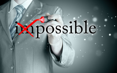 Businessman Hand turning the word Impossible into Possible with