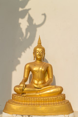 the sitting gold buddha statue under sunlight with deva image