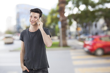 Young man talking mobile phone on street