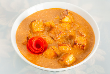 Indian paneer butter masala garnished with tomato peel