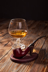 Glass of brandy and a pipe