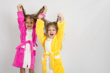 Two girls in the bath robes raised their wet hair