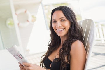 Pretty brunette sitting on a chair and reading magazine