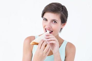 Happy brunette eating sandwich