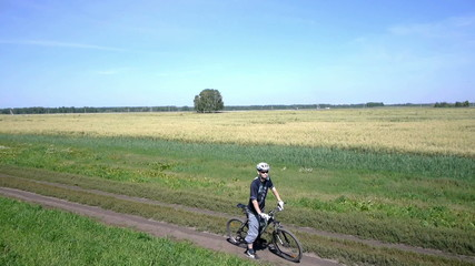 Man cycling on a rural road. Aerial view.