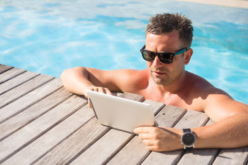 Man using ipad while relaxing in the pool